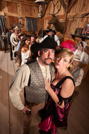 Serious old western couple in crowded saloon photo