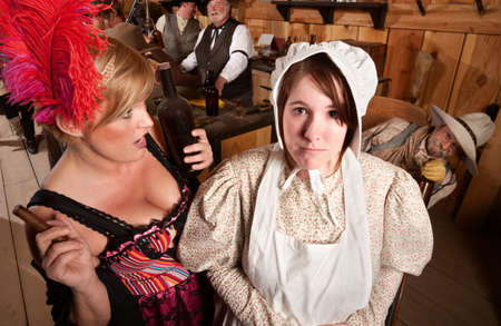 Drunk showgirl talks to young lady in bonnet at old west saloon