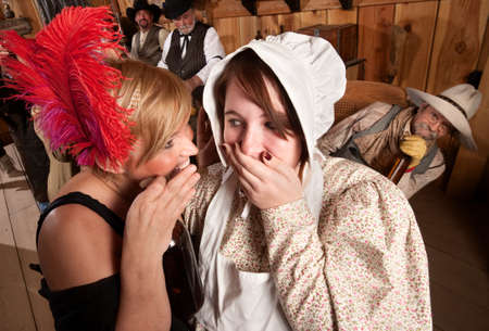 Two ladies whisper to each other as drunk cowboy listens photo