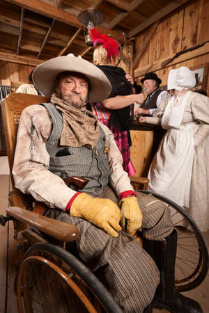 Injured mature cowboy in wheelchair at old west saloon photo