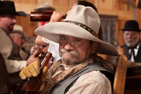 Old cowboy holding whiskey bottle in a saloon photo