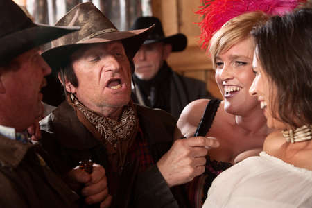 Men and women joke in an old American west saloon Stock Photo - 13791262