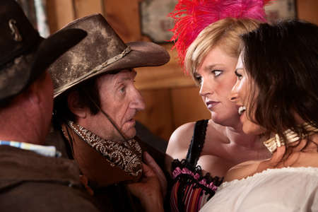 Cowboys talk with women in an old western saloon photo