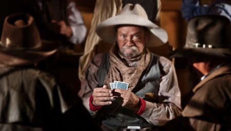 old desk: Bluffing card player in old American west saloon. Hands in focus. Stock Photo