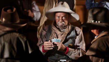 Farol jugador de cartas en el viejo salón del oeste estadounidense. Manos en el enfoque. Foto de archivo - 13791189