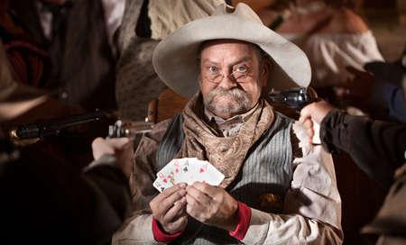 gambler: Gambler with cards and players guns pointed at him