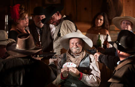 cowboy up: Proud gambler holds winning cards with jealous players