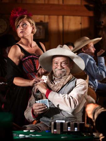 Sneaky alte Pokerspieler wird gewinnen Karte aus Showgirl im Salon Standard-Bild