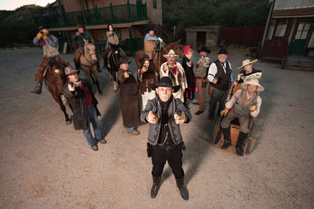 Man with two pistols backed up with a gang in old west costumes photo