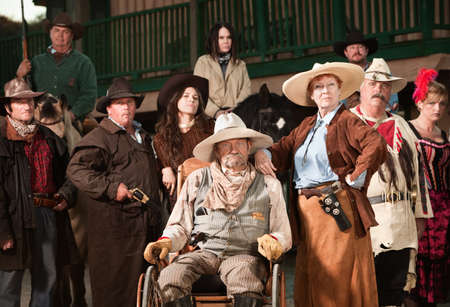 Wheelchair bound cowboy with wife and old west era gang photo