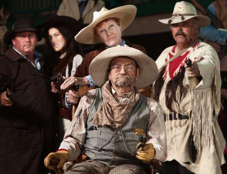 Injured senior cowboy and friends with guns drawn photo