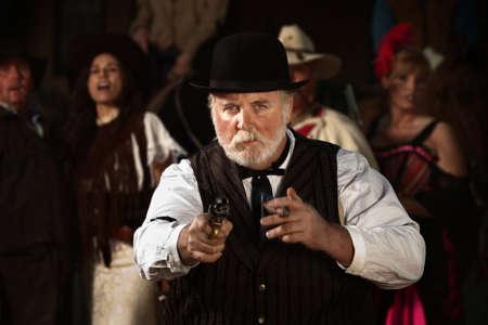 hombre fumando puro: Buscavidas viejo oeste con el cigarro y el arma en la mano Foto de archivo