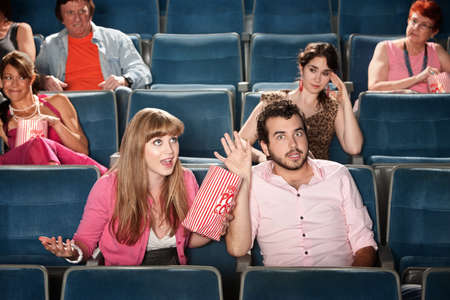 Annoyed audience and arguing couple in movie theater photo
