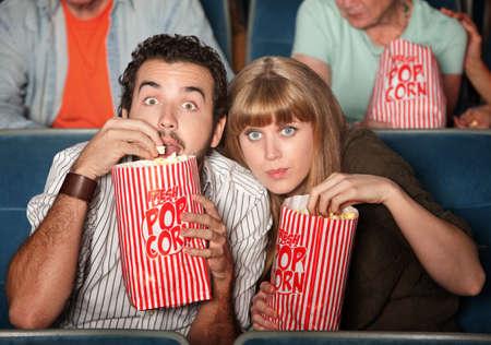 suspenso: Cautivado pareja con bolsas de palomitas de maíz en un teatro