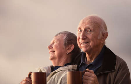 couple married: Elderly man looking over with companion outdoors Stock Photo