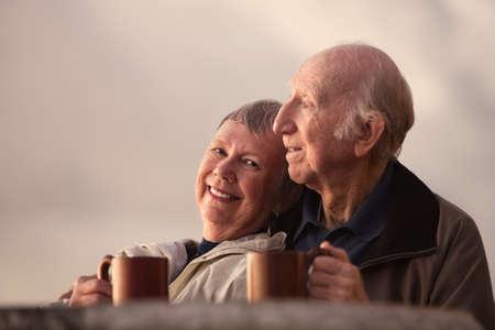 mujer tomando cafe: Sonriente mujer madura con su marido en la escena al aire libre