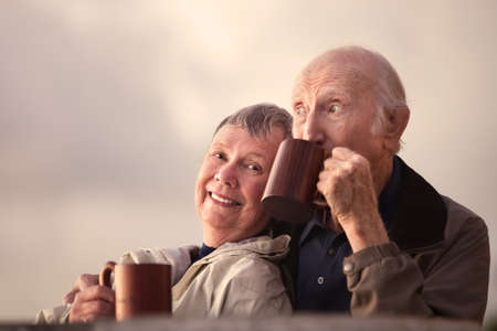 Adorable senior couple outdoors drinking from mugs photo