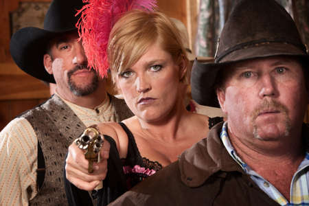 Show girl between two men pulls out a revolver in old west saloon photo