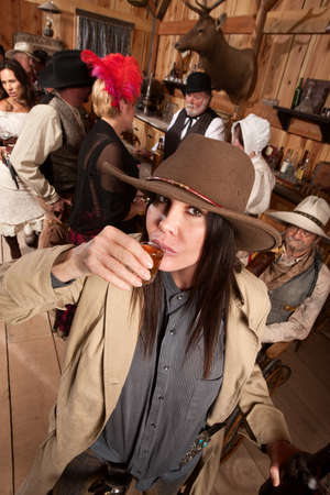 old bar: Woman in cowboy hat and bottle sipping whiskey at a bar