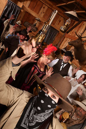 Dangerous female bandit holds up people in old west saloon photo