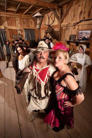 Beautiful bar maid with handsome trapper in saloon photo