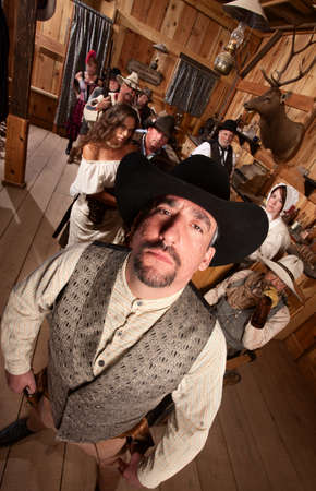 Tough cowboy with hat in crowded old western saloon photo