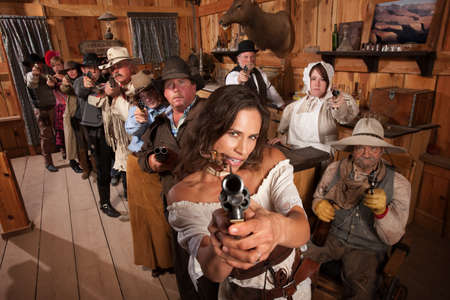 old bar: Pretty Indian gunfighter with revolver and dagger in her mouth Stock Photo