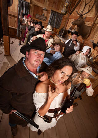 outlaws: Big gunfighter and pretty woman in old western saloon Stock Photo