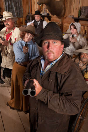 old rifle: Heavyset gunslinger with shotgun in crowded old western saloon