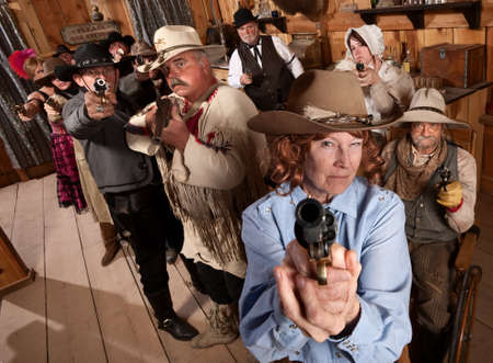 outlaws: Armed senior woman and crowd points guns in old saloon