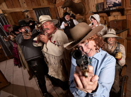 Pretty elderly lady with pistol in old saloon photo