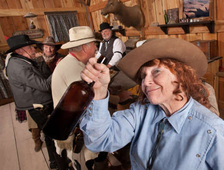 tipsy: Pretty elderly red head with liquor bottle in old saloon