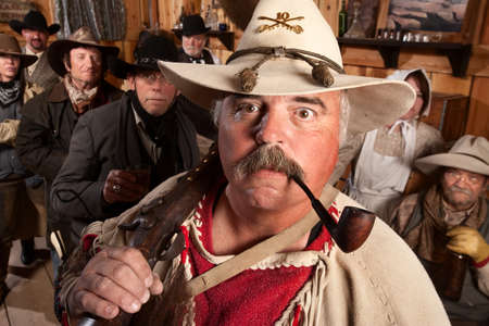 outlaws: Middle aged cowboys in an old western saloon