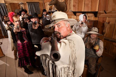 Tough old west desperado and group point their weapons in a bar photo