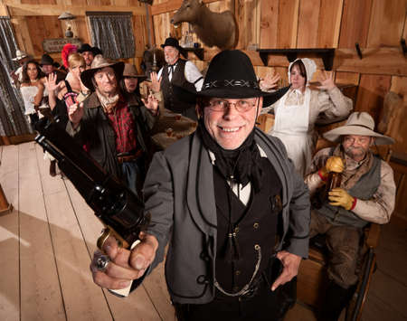 outlaws: Smiling armed sheriff and group of people with hands up in saloon
