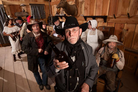 Teleurgesteld sheriff houdt lege fles in het oude westen taverne Stockfoto