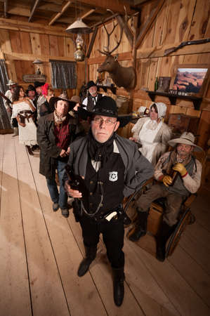 Tough sheriff with sad customers in old American west saloon photo