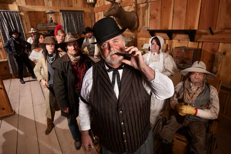 outlaws: Big saloon owner with cigar and customers behind him