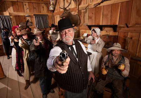 gunfighter: Serious man with old west gang holding guns Stock Photo