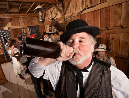 saloon: Borracho resopla una botella de alcohol en un bar