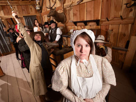 women with guns: Shy woman with rowdy people in an old west saloon Stock Photo