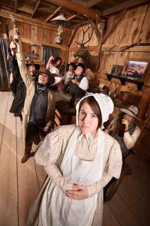 Modest young woman with group of drunks in saloon photo