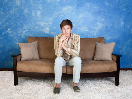 Cute young man sitting in middle of sofa indoors