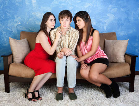 red sofa: Nervous young man with beautiful girls sitting next to him