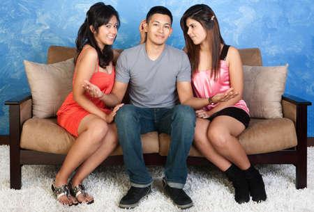trio: Sonriente joven con dos chicas lindas a su lado