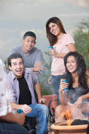Group of teens hanging out at a barbecue drinking soda photo
