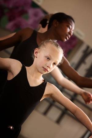 Two young ballet students concentrate in class photo