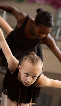 Two cute ballet pupils follow ballet instructions photo