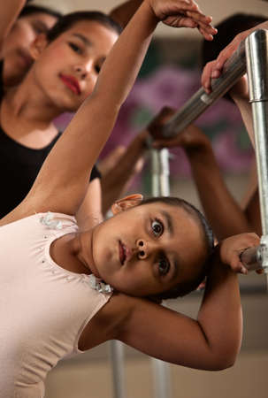 bending over: Cute children on railing practice during ballet class