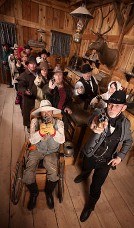 Serious people in old west saloon pull out their weapons photo